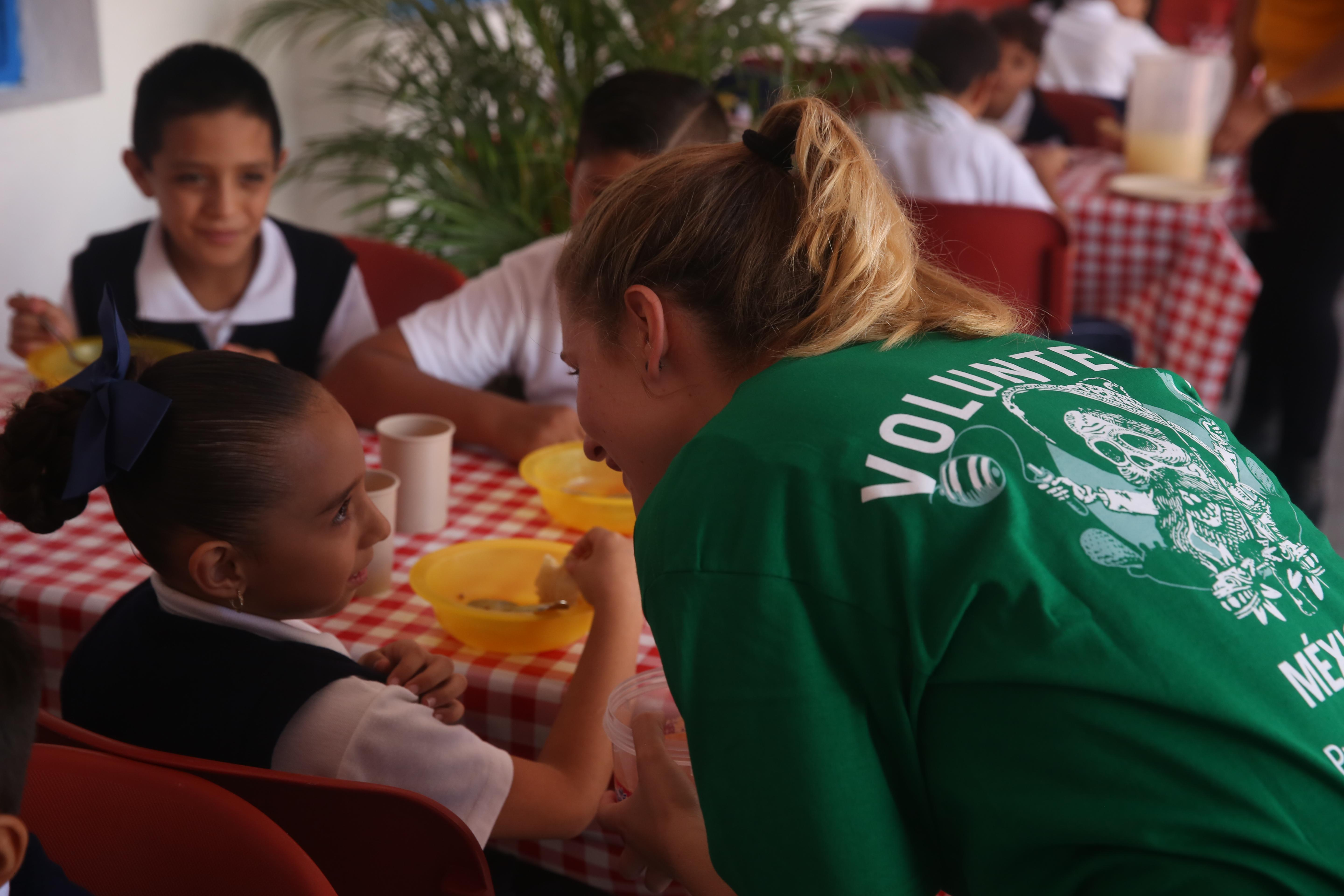 Children practice their English with a Projects Abroad Childcare volunteer while having lunch at a care centre.